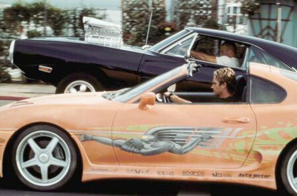 I den sorte bil sidder Vin Diesel og smadrer sin 1970 Dodge Charger igennem, mens den nu afdøde Paul Walker træder sømmet i bund på sin orange Toyota MK IV Supra. I dag er filmen franchiset et af de største med et utal af film til sit navn. Foto: Scanpix