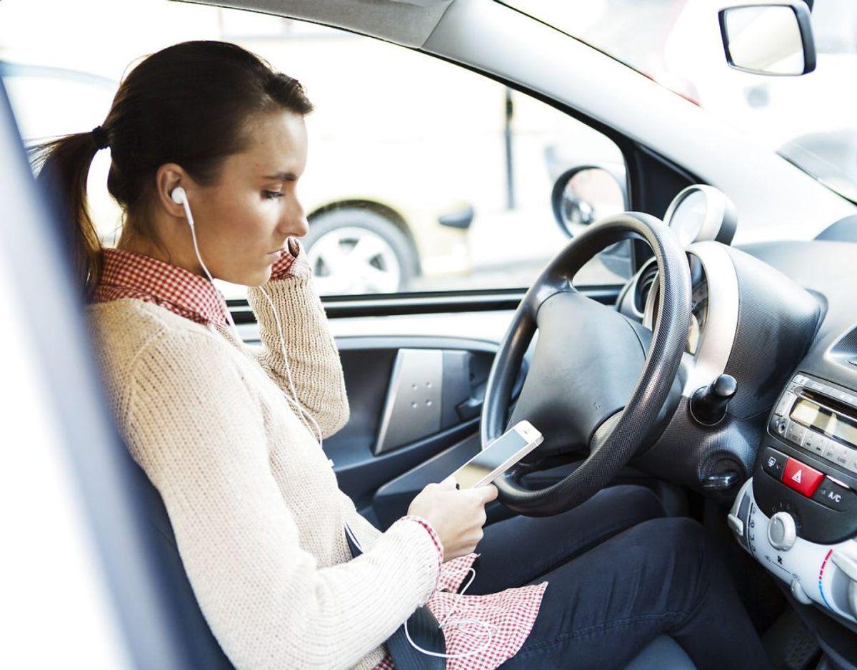 Det er ikke ulovligt at have hovedtelefoner på, mens man kører bil, hvis man ikke betjener sin telefon. Men ifølge Ford er det ikke særlig sikkert. Foto: Scanpix.