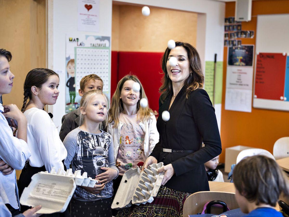 Her ses Kronprinsesse Mary til indvielsen af Nøvling Skole ved Aalborg. Under rundvisningen tog Kronprinsessen del i en læringsleg, der bestod af tennisbolde med tal i æggebakker, hvor man kastede boldene op i luften for så at samle dem igen. Foto: Henning Bagger / Scanpix