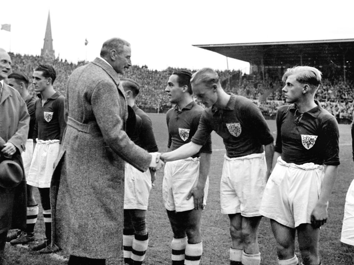 1938: Landskamp i 1938. Kong Christian den 10. trykker spillerne i hånden. Foto: SCANPIX