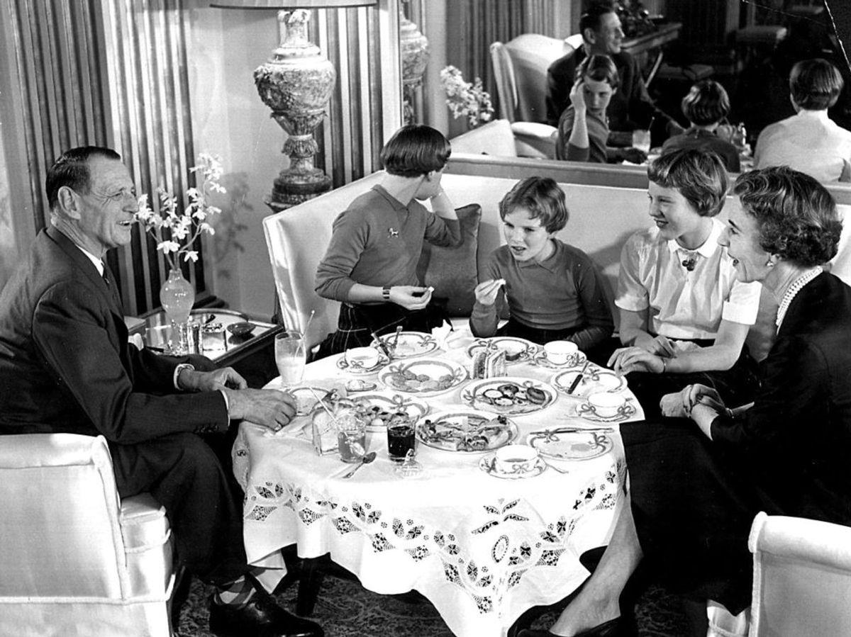 1955: Den danske kongelige famlie ved det store te- og kagebord. Kong Frederik, prinsesse Benedikte som spejler sig, prinsesse Anne-Marie, prinsesse Margrethe og dronning Ingrid. Foto: Vagn Hansen / SCANPIX