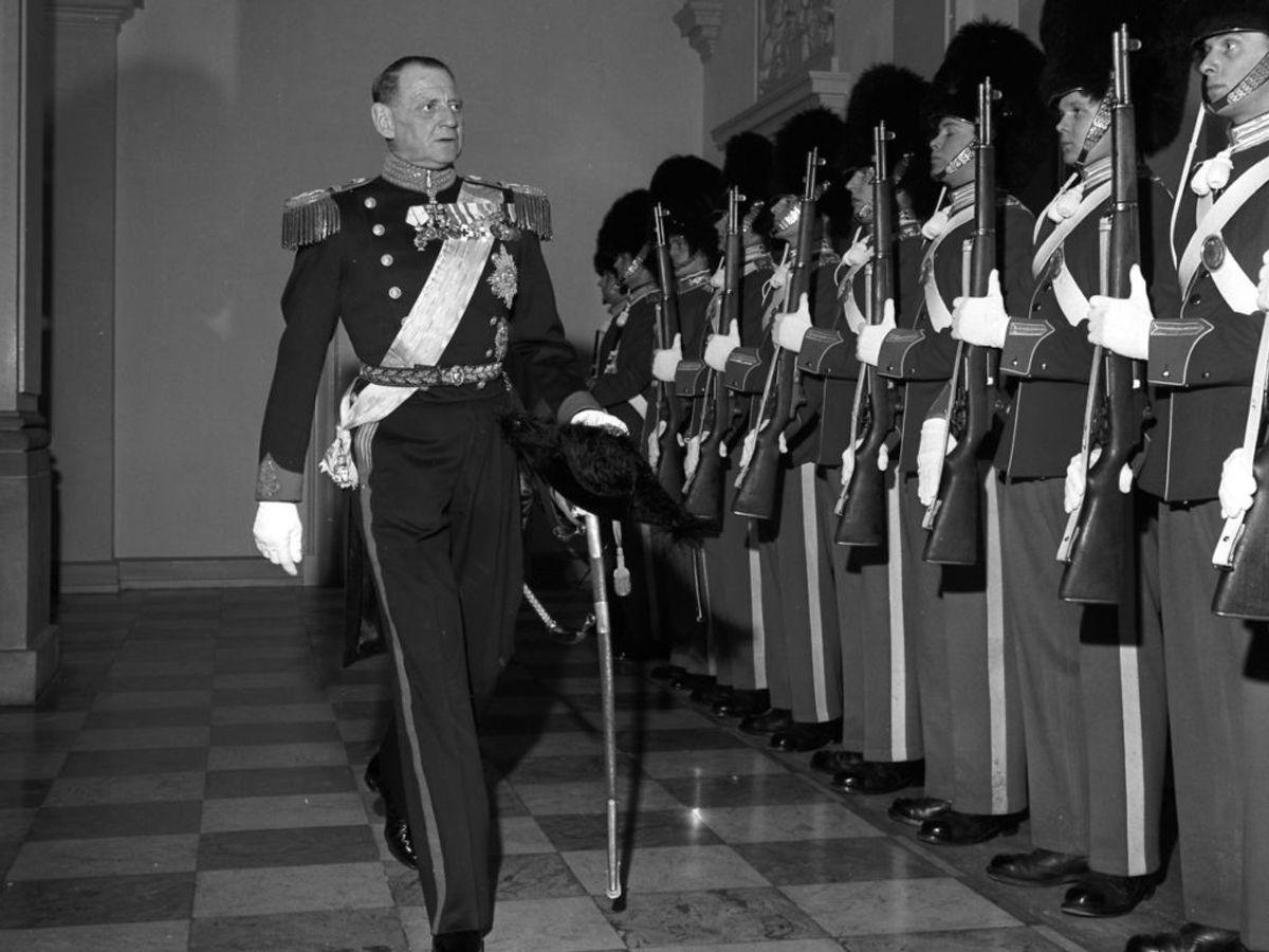 1958: Kong Frederik den 9. passerer livgardens vagt i drabantsalen under Kongeparrets første store aftenselskab på Christiansborg Slot. 500 gæster var inviteret. Foto: Allan Moe / SCANPIX
