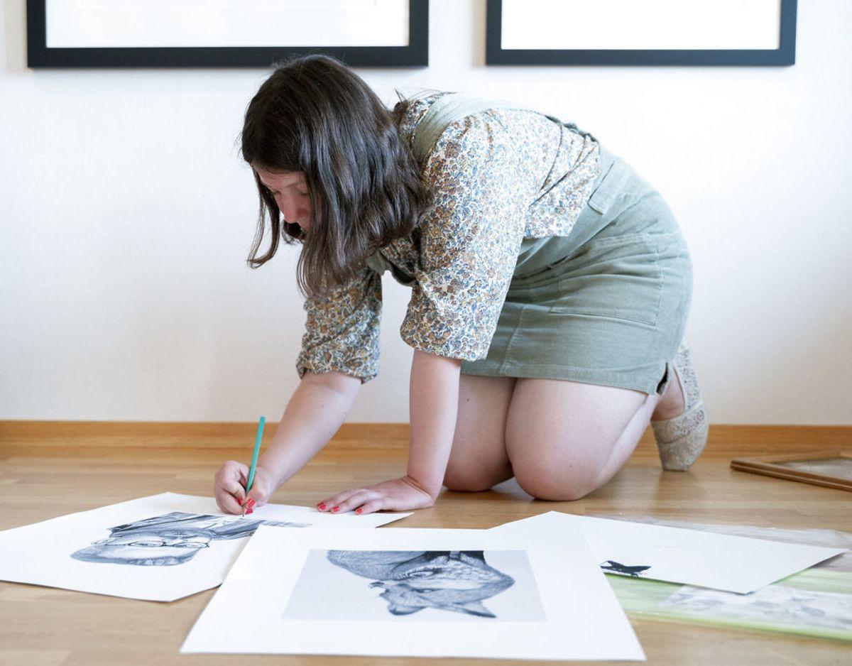 17-årige Maud Angelica, der har lavet et stempel, der bekræfter ægtheden af Ari Behns værker, signerer her en tegning, hun har lavet af sin far. Foto: Fredrik Hagen / NTB scanpix