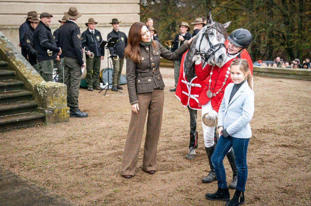 """Kronprinsesse Mary og prinsesse Josephine overrækker præmierne til vinderen af Hubertusjagten 2019 for ponyer i Dyrehaven ved Klampenborg, søndag den 3. november 2019. Hubertusjagten er en symbolsk videreførelse af de gamle parforce-jagter, som Dyrehaven oprindeligt er anlagt til. Her lod man hunde støve ræven op, og feltet fulgte hunde og ræv. I dag er der ingen jagthunde, og ræven er erstattet af to """"forlorne"""" ræve i form af to erfarne ryttere, som rider forrest med rævehaler på deres røde ridejakker. Jagten er ca. 11 km lang og tager 1½ time.. (Foto: Niels Christian Vilmann/Ritzau Scanpix)"""