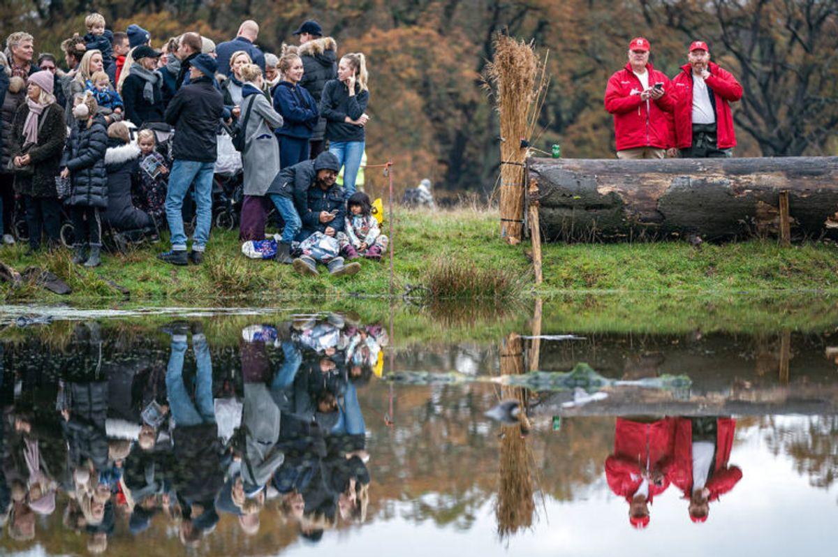 """Tilskuerne venter i spænding på at rytterne skal springe i den berygtede Magasindam under Hubertusjagten 2019 i Dyrehaven ved Klampenborg, søndag den 3. november 2019. Hubertusjagten er en symbolsk videreførelse af de gamle parforce-jagter, som Dyrehaven oprindeligt er anlagt til. Her lod man hunde støve ræven op, og feltet fulgte hunde og ræv. I dag er der ingen jagthunde, og ræven er erstattet af to """"forlorne"""" ræve i form af to erfarne ryttere, som rider forrest med rævehaler på deres røde ridejakker. Jagten er ca. 11 km lang og tager 1½ time.. (Foto: Niels Christian Vilmann/Ritzau Scanpix)"""