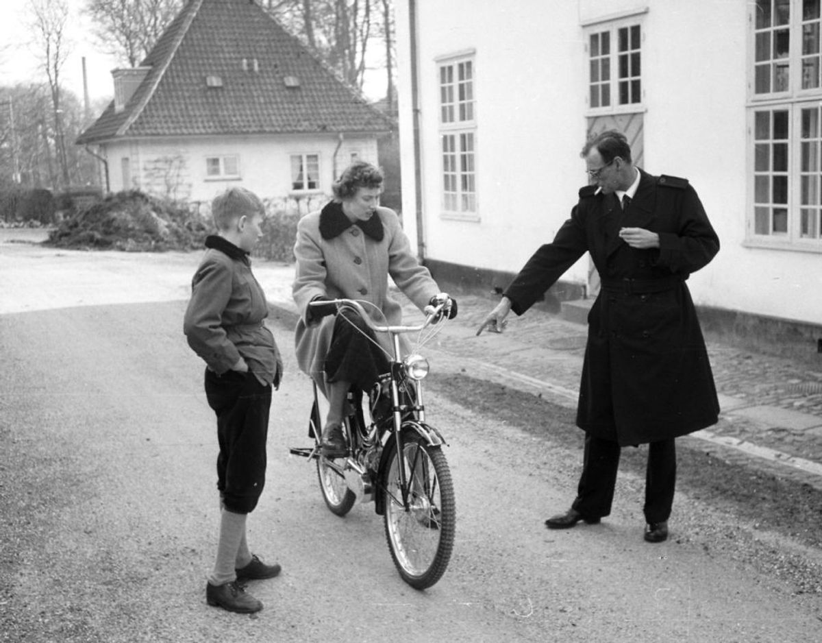 Ved Sorgenfri Slot prøver en ung prinsesse Elisabeth at køre på knallert, mens hendes bror prins Christian og faderen arveprins Knud ser på. Arkivfoto: Scanpix