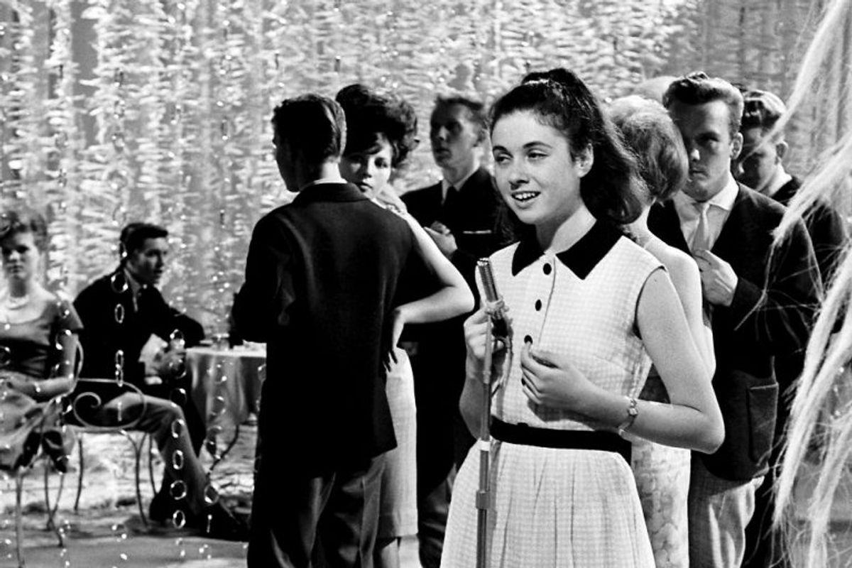 """1964: Årets Melodi Grand Prix blev holdt i København, hvor den kun 16-årige italienske pige Gigliola Cinquetti blev en sikker vinder med sangen Non ho l""""eta. Her er hun sammen med danske teenagere i en tv-udsendelse efter sejren. Foto: Mogens Ladegaard/Scanpix (Arkivfoto)"""