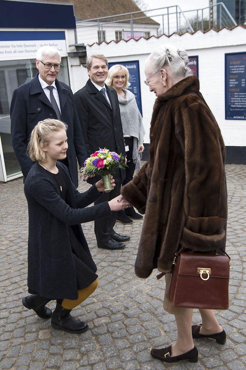 Dronningen hilser på blomsterpigen 11-årige Ester Wowk Vestergaard, museumsdirektør Thomas Bloch Ravn, bestyrelsesformand Peter Kjær og Pernille Bruun, da hun ankommer til åbningen af udstillingen Fra Dronningens Garderobe i Den Gamle By i Aarhus. (Foto: Bo Amstrup/Scanpix 2018)