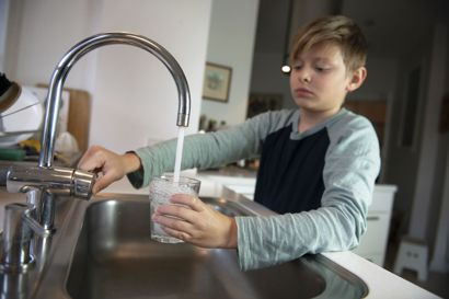 Dreng tager vand i vandglas fra vandhane ved køkkenvask i køkken i lejlighed.