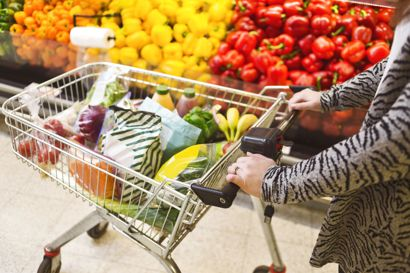 Midsection of woman pushing groceries in shopping cart at supermarket