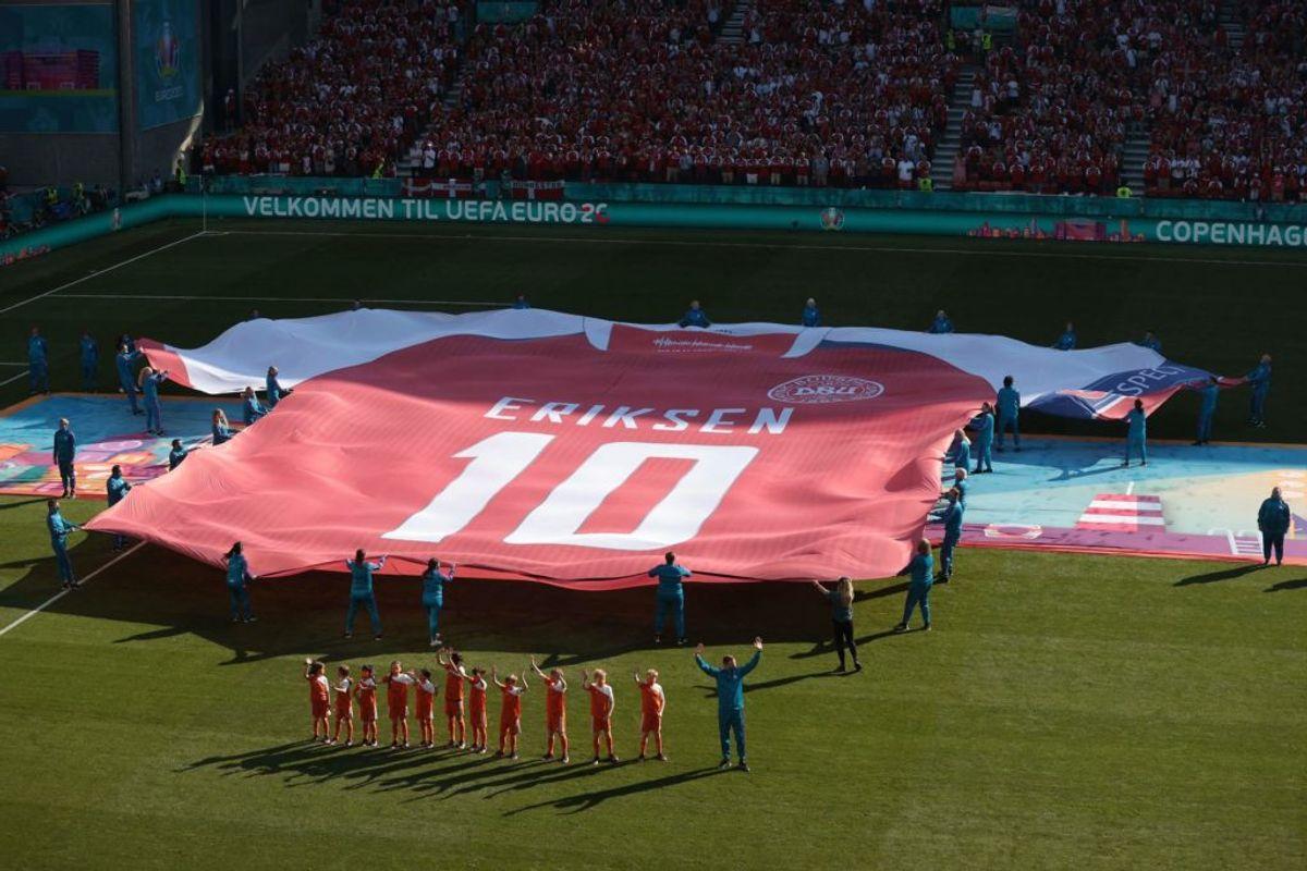 Hyldest til Eriksen før kampen mod Belgien. (Photo by HANNAH MCKAY / POOL / AFP)