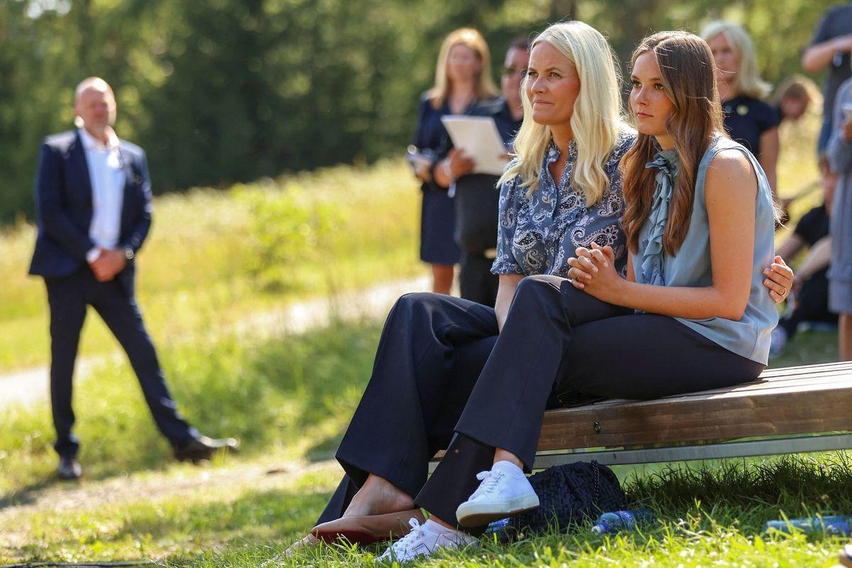 Kronprinsesse Mette-Marit og datteren prinsesse Ingrid Alexandra lytter til ægtemanden og faren, kronprins Haakon, der holder tale på Utøya. Foto: Torstein Bøe / NTB / AFP