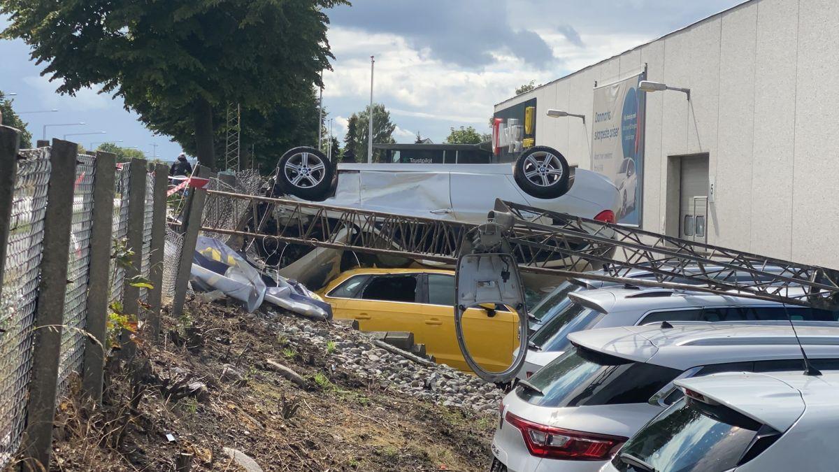 Den hvide bil kørte ind over hegnet og landede på flere biler hos en bilforhandler. Tre er kommet til skade under ulykken.