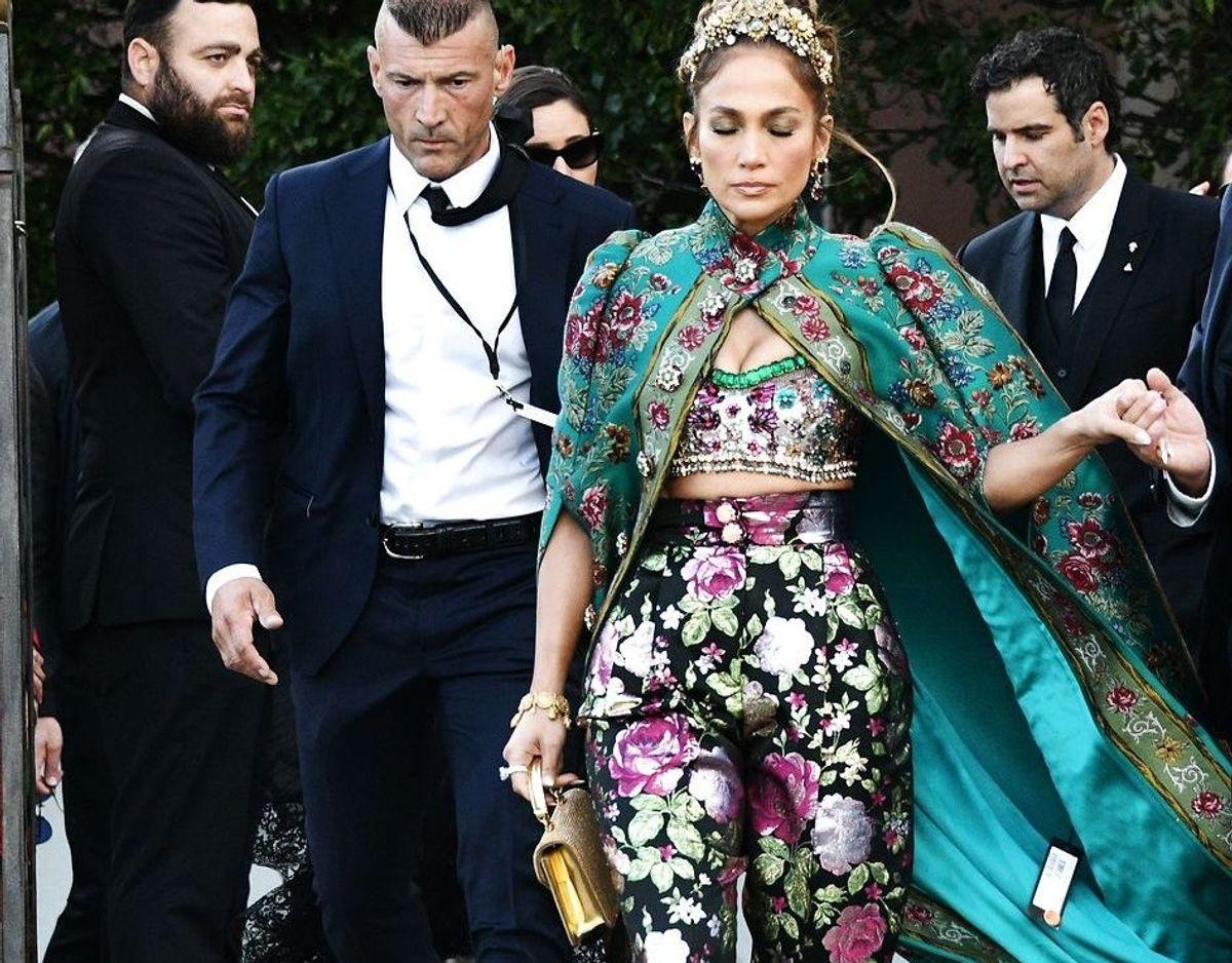 Jennifer Lopez forlader sit hotel - på vej til modeshow. Med kappe og prismærke flagrende.